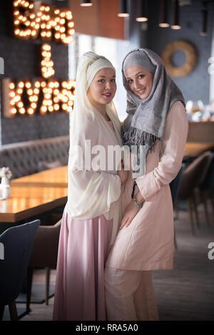 Dos jóvenes musulmanes sonrientes mujeres de pie en la cafetería Foto de stock