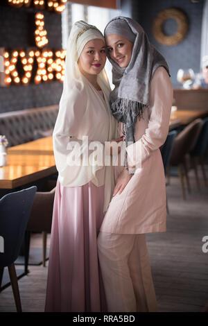 Dos jóvenes musulmanes sonrientes mujeres que llevaban pañuelo en la cabeza de pie en la cafetería. Foto de stock