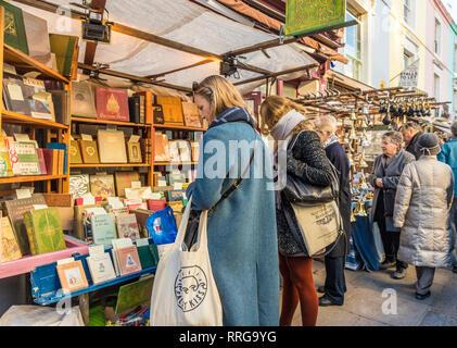 A la gente en un libro antiguo puesto en el mercado de Portobello Road en Notting Hill, Londres, Inglaterra, Reino Unido, Europa