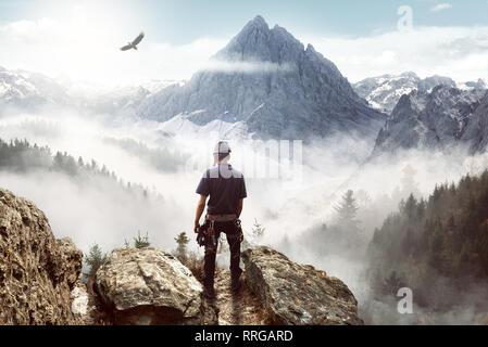 Escalador de jóvenes disfrutando de la vista desde la cima de una montaña
