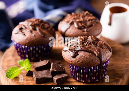 Chocolate muffins o magdalenas decoradas con ganache de chocolate. Acercamiento