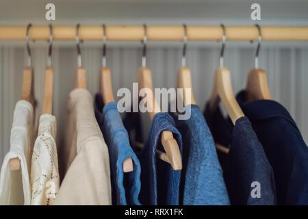 La ropa en perchas en el armario gradiente de blanco a azul oscuro Foto de stock