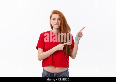 Primer plano de una estricta grave joven viste camisa roja parece estresado y apuntando hacia arriba con el dedo aislado sobre fondo blanco.