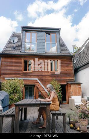 Mujer sentada en la terraza de su casa con el portátil