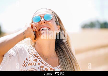 Risa joven rubia en el teléfono usando gafas de sol reflejados