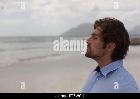 Hombre de pie con los ojos cerrados en la playa