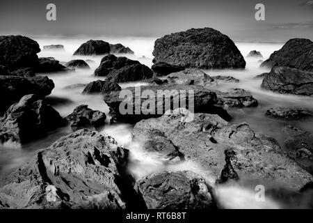 Suavizan las olas por la larga exposición lavar en alrededor de Rocky foreshore en la base del Monte Maunganui, Tauranga Nueva Zelanda Foto de stock