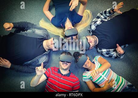 Grupo multirracial de amigos jugando juegos de realidad virtual vr interiores gafas