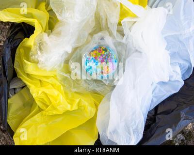 Un globo terrestre o planeta Tierra entre basura y bolsas de plástico. Concepto de ecología