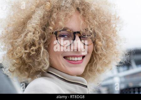 Retrato de mujer rubia sonriendo con tirabuzones llevaba gafas de moda