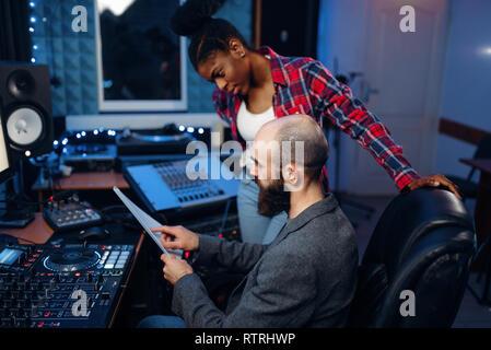 Barbudo ingeniero de sonido en el panel de control remoto de audio en estudio de grabación. Músico en el mezclador, mezcla de música profesional