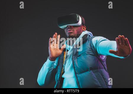 Concepto de juego. Hombre casual africanos en caliente al aire libre en temporada vistiendo ropa móvil auricular VR disfrutando nueva realidad en una habitación oscura. Moda y Innovatio