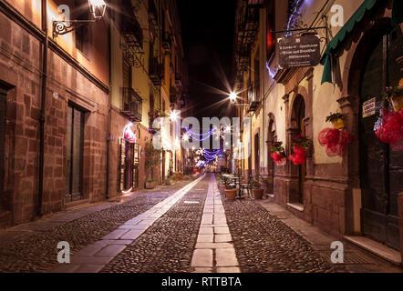 Bosa, isla Cerdeña Italia - 29 de diciembre de 2019: turista relajarse durante la noche en las antiguas calles de Bosa, Cerdeña, Italia