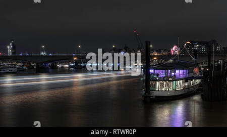Waterloo Bridge con barco en el río Támesis. Riverside de la noche Londinense.