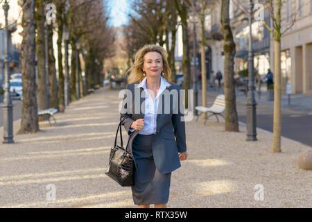 Elegante mujer rubia madura profesional caminando con su bolso por una calle de la ciudad en un paseo arbolado