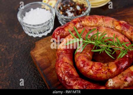 O asado a la parrilla espiral salchichas de cerdo con romero, sal y peper en madera tabla de cortar.