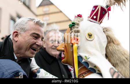 """Rottweil, Alemania. 04 Mar, 2019. Un Geschell, un Rottweiler fool figura, conversa con el presidente de la CDU y el ministro del interior de Baden-Württemberg, Thomas Strobl (l). Con gritos y la llamada 'Hu-hu-hu-hu-hu-hu"""" alrededor de 4000 tontos fueron sacados a través del centro de la ciudad delante de miles de visitantes. El Rottweiler Narrensprung es uno de los destaques del Swabian-Alemannic carnaval y uno de los desfiles tradicionales en el suroeste. Crédito: Patrick Seeger/dpa/Alamy Live News"""