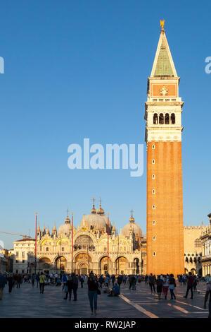 Sunet dorado a través de la Basílica de San Marcos y el Campanile, en Piazza San Marco, Venecia, Véneto, Italia con los turistas en esta popular atracción turística