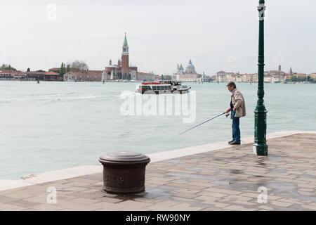 Un hombre anciano pescando en Venecia. Un pescador en el canal de Venecia. Italia