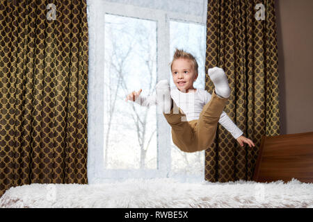 Niño fun home. Niño alegre en movimiento saltando riendo en la cama. Niño de 6 años felizmente juega por la mañana en la sala.