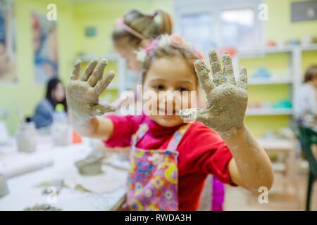 Retrato de niña en clases de alfarería taller de artes muestran las manos después de moldeo de barro arcilloso.