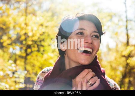 Mujer sonriente en bosque otoñal Foto de stock