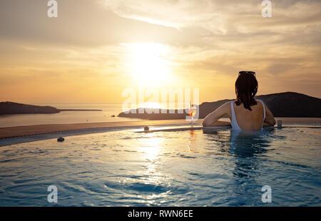 Mujer relajante al borde de la piscina infinita al atardecer Foto de stock