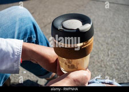 Primer plano de un joven de manos y vistiendo jeans rajados sosteniendo su café en un KeepCup reutilizables