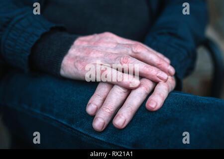 Central de altos hombre en ropa de abrigo, sentado en un banco Foto de stock