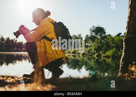 Vista lateral de un viajero ajustando su cámara digital sentado junto a un lago. Hombre mirando su cámara DSLR mientras toma fotografías en exteriores con sol en th
