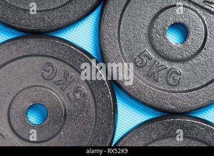 Placas de peso en una colorida planta azul dentro de un entrenamiento con pesas gimnasio / Fitness Studio