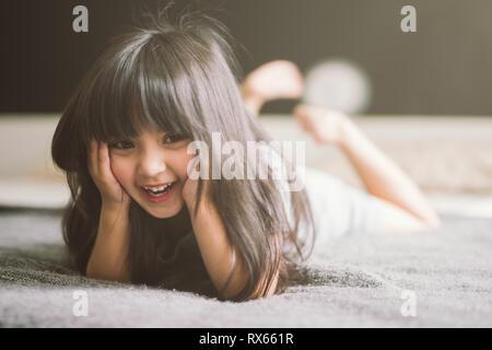 Feliz niña acostado en la cama Foto de stock