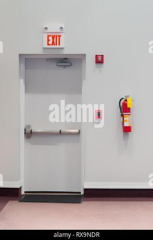 Disparo vertical de una puerta de salida de emergencia con una alarma de incendio, extintor de fuego, y una luz de emergencia en la pared junto a él.