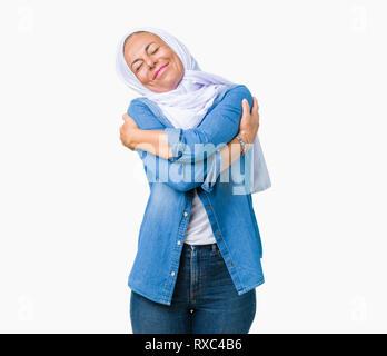 Edad media árabe oriental mujer vistiendo arabian hijab sobre antecedentes aislados abrazarse a sí mismo feliz y positivo, sonriente, confiado. El amor propio y la auto Foto de stock