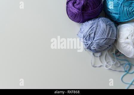 Vista desde arriba en las coloridas bolas de hilo para tejer a mano aislado sobre fondo blanco de mesa.