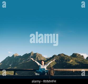 Mujer Asiática viajero sentado y brazos arriba en el aire en el punto de vista de la terraza con vistas al paisaje de montaña con nube y cielo azul en día soleado en fores