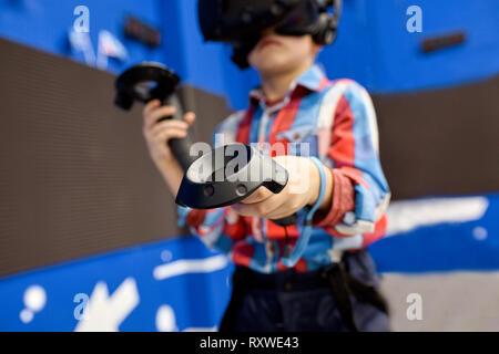La tecnología moderna, los juegos y la gente concepto - boy en casco de realidad virtual o gafas 3D jugar a videojuegos Game Center