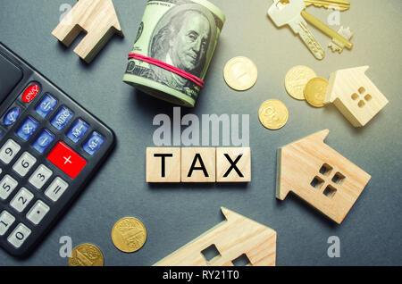 Casas de madera, una calculadora, llaves, monedas y bloques con la palabra impuestos. Los impuestos a la propiedad. Cálculo de interés impuesto sobre la vivienda. Pena, atrasos. Regis Foto de stock