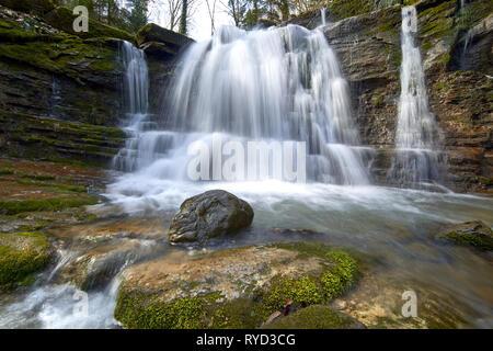 Cascada de un río de montaña con rocas cubiertas de musgo