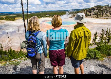 Dos mujeres y un hombre de pie sobre una colina por encima de la Grand Prismatic Hotspring en el Parque Nacional Yellowstone, Wyoming, Estados Unidos.