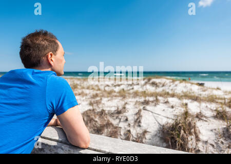Destin Miramar Beach Village de la ciudad de Florida en el Golfo de México con el océano de joven closeup con camisa azul inclinado sobre la baranda de cerco