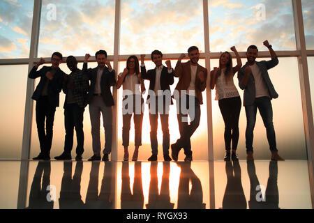 Grupo de jóvenes profesionales de pie en una oficina con una ventana grande