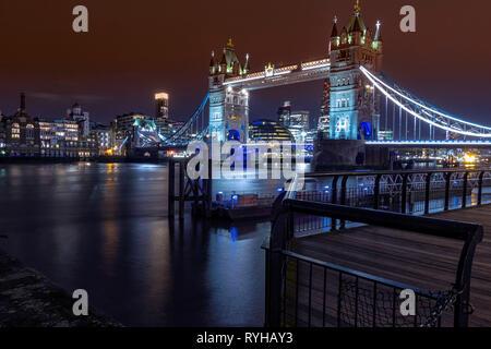 Tower Bridge, Londres, Inglaterra. El 13 de marzo de 2019. Una gran foto del famoso puente sobre el Río Támesis en la noche con edificios iluminados y aguas tranquilas