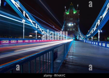 Tower Bridge, Londres, Inglaterra. El 13 de marzo de 2019. El icónico puente que cruza el río Támesis por la noche, mostrando una de las famosas torres, con coche estelas de luz en Foto de stock