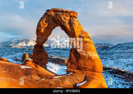 Icónico Arco delicado iluminado con luz hora dorada brillante con las montañas La Sal detrás de febrero de 2019 después de una tormenta de nieve en el Parque Nacional de Arches, Moab,