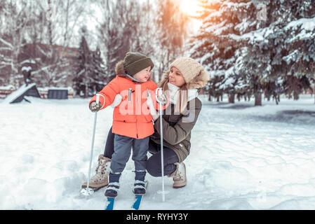 Una joven mujer, madre apoya con cuidado, muchachito hijo de 3-6 años, el esquí en invierno Forest Park. Las primeras lecciones de deportes en la calle. Feliz
