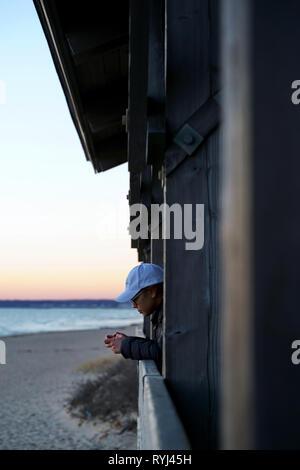 Un solitario joven sunset surf en un refugio campestre, mientras que en una popular playa del parque estatal.