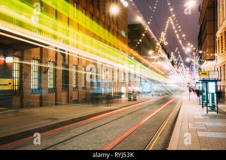 Helsinki, Finlandia - 11 de diciembre de 2016: El tranvía sale en el desenfoque de movimiento desde la parada en la calle Aleksanterinkatu En distrito Kluuvi en la tarde noche de Navidad Foto de stock