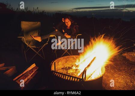 Joven Mujer reflexiva con botella de cerveza está sola cerca de la hoguera y leña en la noche. Barefoot tristeza chica busca en fuego brillante en la oscuridad.