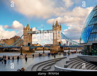 Londres, Inglaterra - 10 de marzo de 2019: hermosa vista del Tower Bridge de Londres más con los turistas que caminan a la orilla del río al atardecer